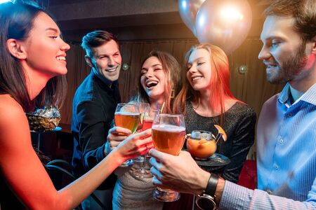 young friends drink and have fun togeher in karaoke bar, beautiful girls and handsome guys chilling out and rocking together, have leisure time