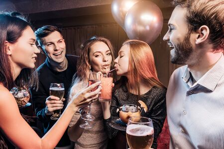 good-looking cheerful happy young people have party time in karaoke bar, wearing party dresses and shirts. Holiday, celebration, party concept