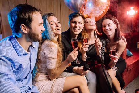group of young caucasian people in party clothes have free time. leisure time in karaoke bar, enjoy singing, drinking