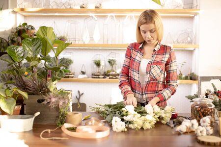 Photo pour Small business owner and beautiful florist woman preparing a white flower bouquet, enjoy working with plants and flowers. Botany, plants concept - image libre de droit