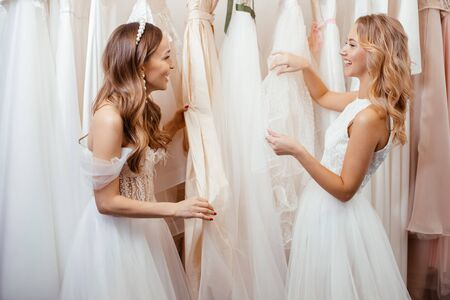 Photo pour young caucasian friends choosing, trying on wedding dresses in salon, beautiful women preparing for wedding, to celebrate, dream to be bride - image libre de droit