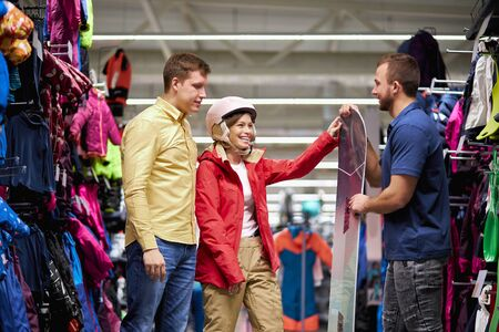 Photo pour young caucasian customers came in sportswear store to make purchase, handsome guy and woman get involved in various sport, huge. large assortment of goods around - image libre de droit