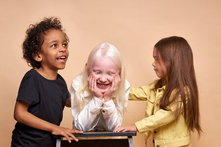 Photo for portrait of cheerful positive kids, multiethnic children isolated in studio. adorable afro boy and albino, caucasian girls stand together, posing. international friendship - Royalty Free Image