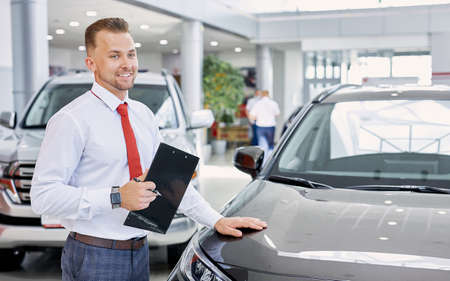Photo pour portrait of smiling car dealer at work, man in white formal shirt ready to talk about cars, automobiles and their chaacteristics to customers - image libre de droit