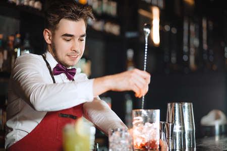 Photo pour Barman holding a long spoon and glass filled with ice cubes and red drink mixing the beverage on the bar counter of night club - image libre de droit