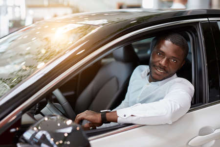 Photo pour handsome rich african man try himself behind the wheel of new automobile, man likes it, gong to buy - image libre de droit