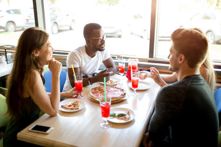 Multiracial young friends gathering for celebrating b-day of their afro american friend. Cheerful people having tasty pizza and fruit non alcoholic coctails at the indoor party.