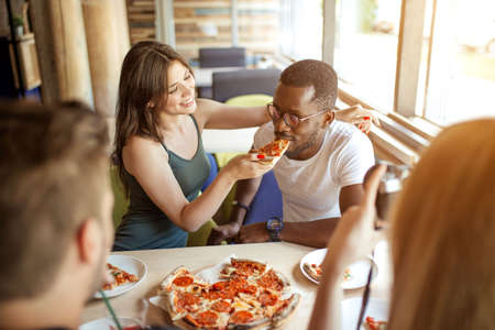 Photo for Young multiracial diverse colleagues eating pizza during their lunch time at office pizzeria, playing team building game, feeding his partner with tasty pizza - Royalty Free Image