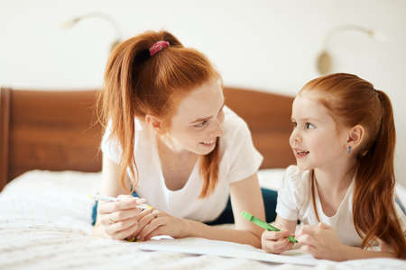 Photo pour family, children and happy people concept - Close-up view of beautiful caucasian red-haired mother and daughter drawing a card for Daddy s b-day while lying on white bed, creative holydays with kids. - image libre de droit