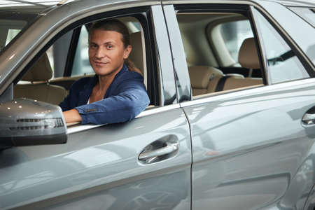 Photo pour Confident business man sitting in his new car at the dealership with his hands on the steering wheel, looking at camera. - image libre de droit