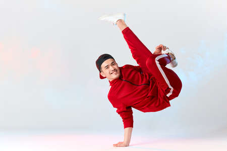 Photo pour Stylish dressed in red sweatpants asian b-boy is performing kick in air, standing on hands while dancing break dance on white background. Freestyler doing air baby freeze - image libre de droit