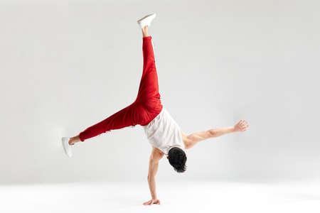 Foto de Break dancer doing handstand stunt on one hand and splitted out legs over white studio background - Imagen libre de derechos