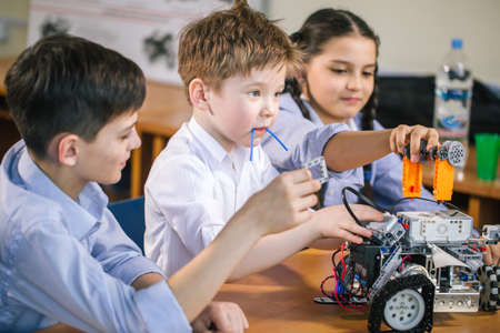 Photo for Happy little inventor kids fit the separate component parts of technical toy together, add electronic chips and have ready made robotic car toy - Royalty Free Image