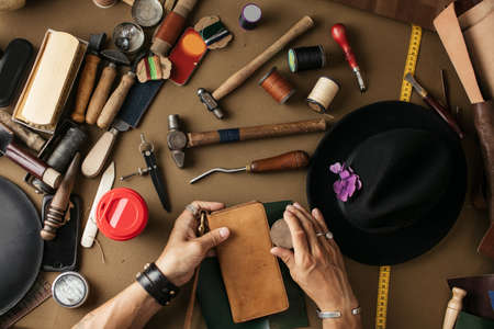 Photo pour Close-up of male master cutting piece of leather with crafting tools for future wallet at workshop. High angle view of cobbler working place. - image libre de droit