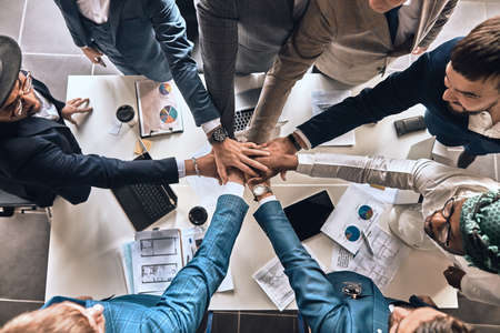 Foto für young diverse people standing with folded hands together. top view photo. friendship, partnership, togetherness. - Lizenzfreies Bild