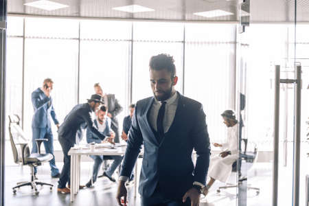 Photo pour Young business man in formal suit leaving the boardroom with people conducting negotiations at table - image libre de droit