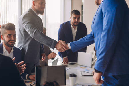 Photo pour Business people in formal wear shaking hands, finishing up a meeting, establishing multi-ethnic partnership, making deal. - image libre de droit