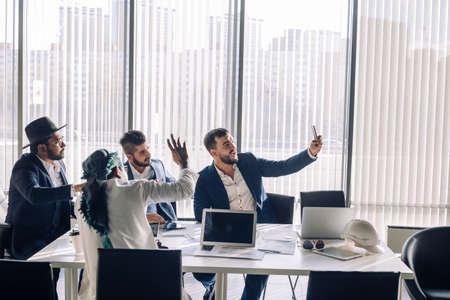 Photo for Positive caucasian bearded businessman taking selfie with his middle eastern and indian partners during workday, sitting in conference room. - Royalty Free Image