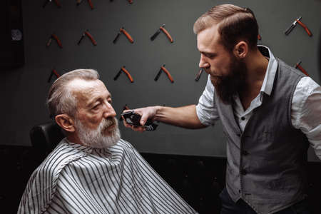 Foto für Close up of a hairdresser s work for a handsome respectable old-aged bearded man at the barber shop. He is doing styling with the electric shaver. - Lizenzfreies Bild