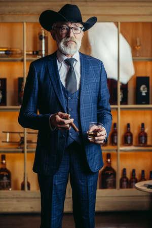 Foto de Portrait of old-aged male dandy dressed in elegant trendy men s suit in big hat smokes cigar and drinks alcoholic beverage. - Imagen libre de derechos