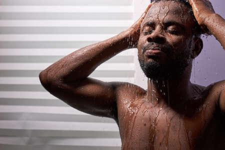 Photo pour good looking man wet taking shower in bath - image libre de droit