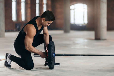 Photo for attractive sportsman preparing disk for powerlifting, weightlifting. full length side view photo. preparation of sport equipment. copy space - Royalty Free Image