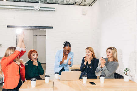 Foto de diversity, race, height, success and people concept - multi-ethnic group of happy women clapping hands and giving high five at jubilation at her success or victory. - Imagen libre de derechos