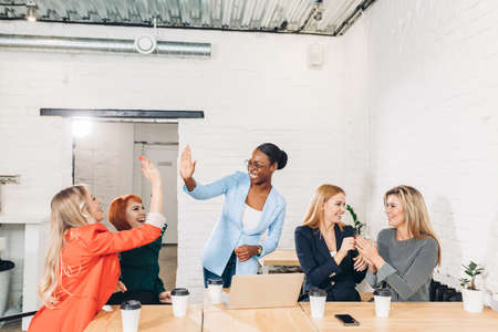 Foto de diversity, race, height, success and people concept - multi-ethnic group of happy women clapping hands and giving high five at jubilation at success or victory. - Imagen libre de derechos