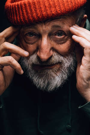 Photo for Close up portrait of bearded old man in orange hat with wrinkled weathered face stares hopefully at camera holding hands near the temples, isolated over black background. Human emotions concept. - Royalty Free Image