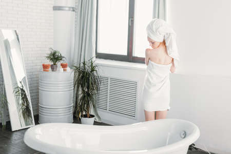 Foto de Beautiful young red-haired slim woman covering her body with towel and smiling while standing near the bathtub in spacious modern bathroom with green plants and window. - Imagen libre de derechos