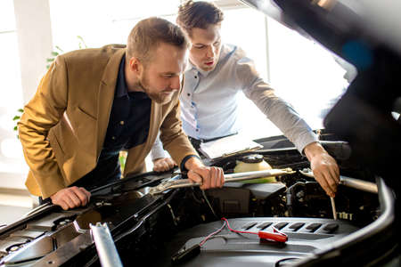 Photo pour caucasian salesman and consultant look at the hood assemble in car. perfect business class auto represented in dealership - image libre de droit