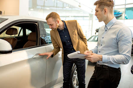 Photo pour affable handsome caucasian consultant and client in dealership. young business man came to buy new automobile, happy future owner of representative car - image libre de droit