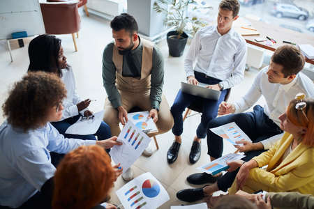 Photo pour Modern and enthusiastic business people sit in circle discussing business ideas, steps for building business, using diagrams and papers. - image libre de droit