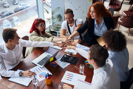 Photo for Positive group of co-workers joined hands together finishing up successful business meeting in conference office, papers, colorful pencils on table. Creative workers - Royalty Free Image