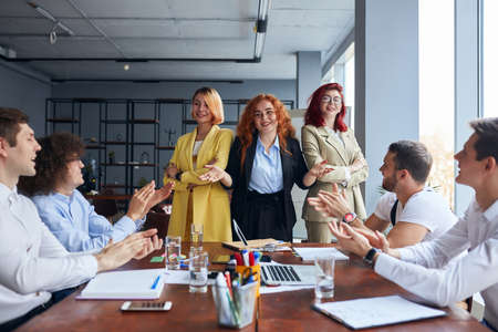 Photo pour Back to back of three businesswomen standing near table,men colleagues look at them and clapping hands, congratulate. co-workers women and men together working on project, proffesional occupation. - image libre de droit