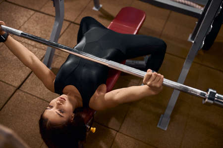 Photo for Beautiful powerlifter with strong arms lifting weights in sports hall, looking away, holding iron bar, exercising with heavy barbell, training hard for competition of weightlifting, high angle shot - Royalty Free Image