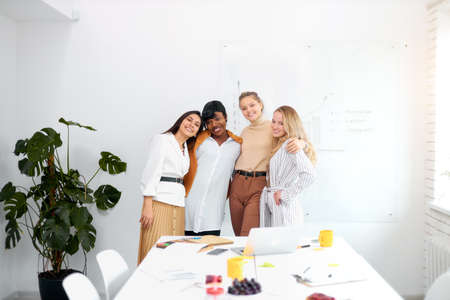 Photo pour attractive four caucasian and african women hugging each other look at camera, good teamwork. business people concept - image libre de droit