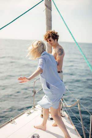 Photo for Blonde girl in company with her friend stand on bow of a white yacht, while the curly man helps her, both being in good mood. - Royalty Free Image