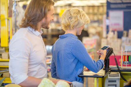 Photo for it could be much more easier for young people, youngsters, to check out at the grocery counter, retailer, with credit card. - Royalty Free Image