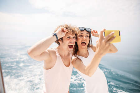Photo pour Happy caucasian couple taking selfie photo over beautiful sea background. Romantic lovers, woman and man traveling on yacht sailing vacation. - image libre de droit