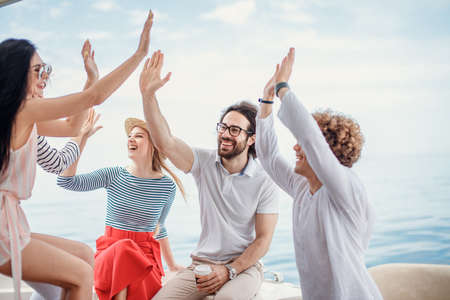 Photo for Group of friends, dressed in casual cloth, giving high five on a fashionable yacht - Happy people having a fancy party on a luxury boat - Royalty Free Image