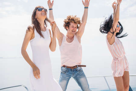 Photo for playful , caucasian heterosexual friends dancing on a bow of yacht , hot dancing against blue sea background with copyspace . Beautifyl youngsters. - Royalty Free Image