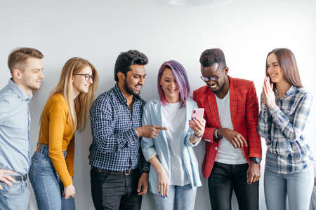 Photo pour Group of Multicoloured joyful people standing against white wall. Caucasian woman with violet hair showing photos on smartphone to her diverse friends. Technology concept with young users people. - image libre de droit