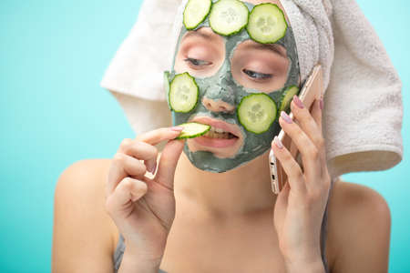 Foto de Healthy skin and body care, complexion treatment at home concept. Caucasian woman speaking with her mother via phone, having grey mud mask with slices of cucumbers on her face - Imagen libre de derechos