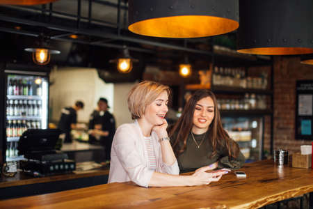 Photo pour Two attractive excited young using smartphone while sitting at the cafe with cosy stylish interior - image libre de droit