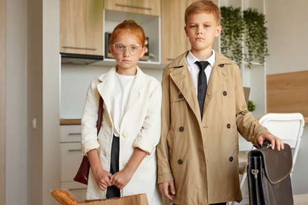 Photo pour portrait of confident kids couple pretend to be adults, young business boy and girl in formal wear seriously look at camera, indoors - image libre de droit