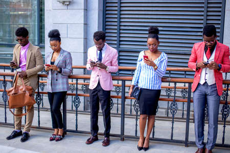 Photo pour african students playing network games online. entertainment concept.everybody is gazing at mobile phones. stylish people with modern gadgets - image libre de droit