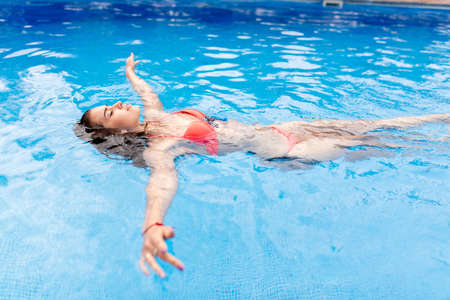 Photo pour feeling of relaxation. young gorgeous female doing exercises on the water in the pool. pretty tourist concentrated on swimming - image libre de droit