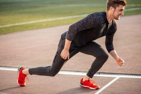 Foto de young male athlete launching start line in race track - Imagen libre de derechos