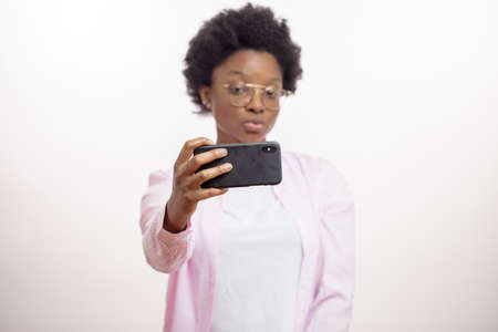 pretty young afro woman posing to her cell phone. african stylish female looking at the screen of the gadget. isolated white background. studio shot